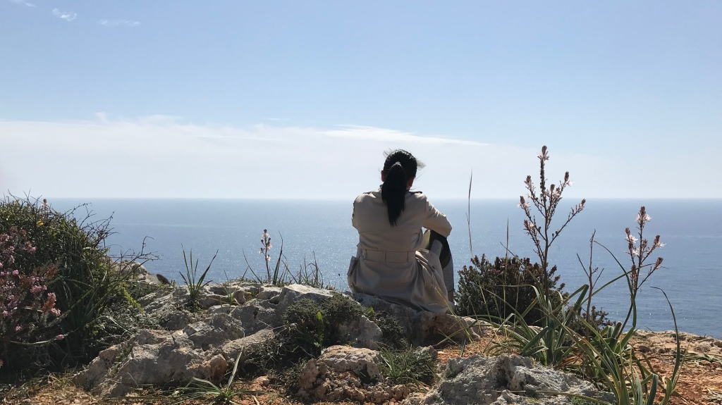 photo of woman sitting above a cliff overlooking the Mediterranean Sea